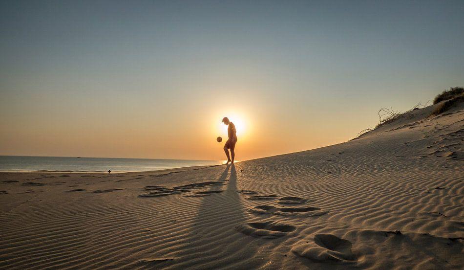 Strand voetbal tijdens zonsondergang  van Abe Raats
