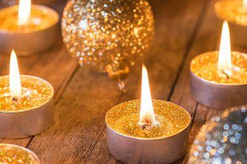 Feestelijk brandende gouden advents- en kerstkaarsen met glinsterende ballen decoratie van Alex Winter