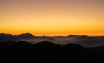 Oranje zonsondergang over mistige Alpen van Kaj Hendriks