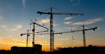 Hijskranen bij zonsopkomst op een bouwplaats van Marcel van den Bos