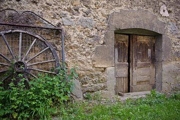 Muur oude deur wagenwiel van Rene du Chatenier