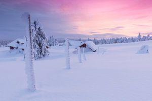 Ondergesneeuwd  dorp tijdens pastelkleurige zonsondergang van
