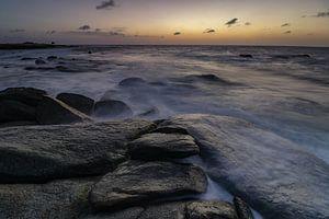 Golven slaan over de rotskust aan de noordkust van Aruba tijdens zonsondergang