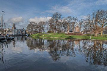 De Leeuwarder stadsgracht met twee kerktorens en bomen weerspiegeld in de late herfstzon van Harrie Muis