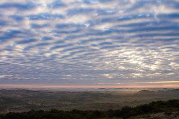 wolkendek met doorbrekende zon boven duinen met mist van Menno van Duijn