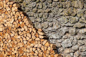 Pile de bois de chauffage devant un mur en pierre naturelle sur Fartifos