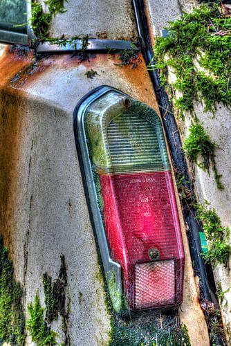 achterlicht bedekt met mos van een sloopwagen van