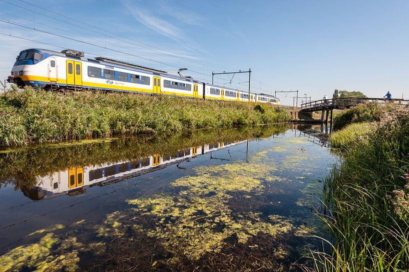 Der Zug in der holländischen Landschaft: Oostzaan (Reflexion) von John Verbruggen