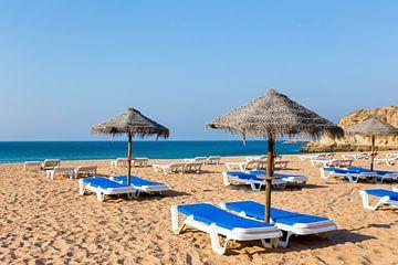 Gruppe Sonnenschirme und blaue Sonnenbetten auf Strand in Albufeira Portugal von