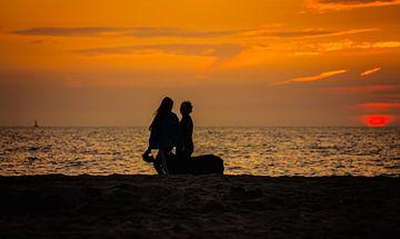 strandwandeling met een in de zee verdwijnende zon van Moo pix