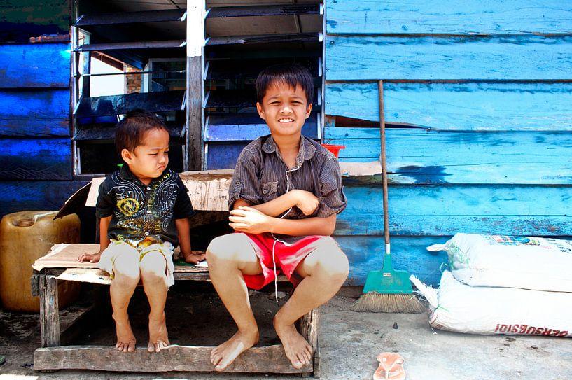 Indonesische kinderen met op de achtergrond een blauw huis van André van Bel