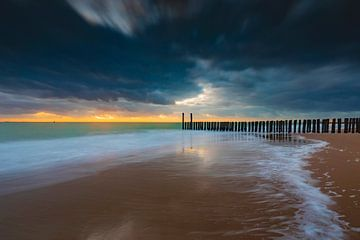 Hollandse wolkenlucht en typische golfbreker van houten palen langs de Zeeuwse kust van gaps photography