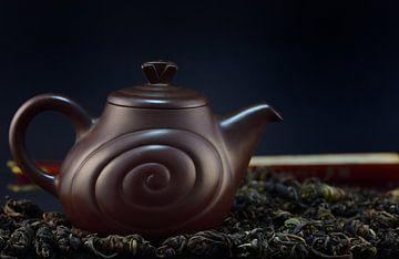 Een bruine theepot van klei met thee van Ulrike Leone