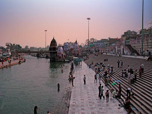 Mensen baden in de heilige rivier de Ganges bij zonsondergang in Haridwar India van