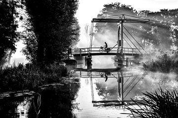Eenzame krantenbezorger fietst over een brug in IJlst Friesland. One2expose Wout Kok Photography.  van