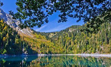 Berge, grüne Fichten und Laubbäume spiegeln sich im klaren Wasser eines Bergsees. Der Herbst, von Michael Semenov