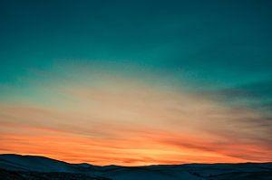 Zonsondergang boven besneeuwde heuveltoppen