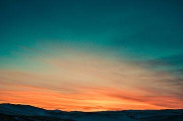 Zonsondergang boven besneeuwde heuveltoppen van Roger VDB