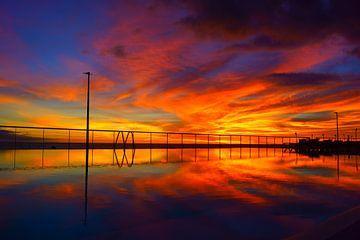 Kleurrijke zonsondergang aan een zwembad van Michel van Kooten