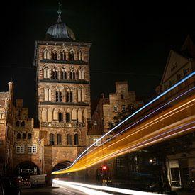 Traces lumineuses d'un bus traversant la tour de la porte Burgtor de Lübeck la nuit, bâtiment histor sur Maren Winter