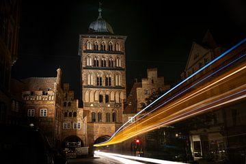 Lichtsporen van een bus die 's nachts door de poorttoren Burgtor van Lübeck rijdt, historisch bakste