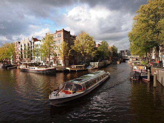 Rondvaartboot in kanaal met grachtenpanden in de achtergrond, Amsterdam, Nederland