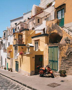 Scooter in de straten van het Italiaanse eiland Procida met de gekleurde traditionele huisjes van Michiel Dros