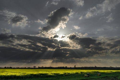 zon door wolkenlucht boven koolzaadveld  von huub claessens