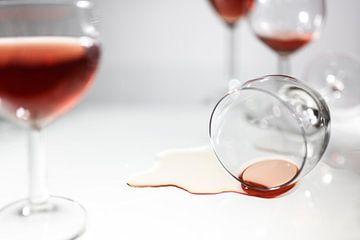Omgekeerd drinkglas met een plas rode wijn tussen wazig staande glazen, concept voor feestvreugde, a van Maren Winter