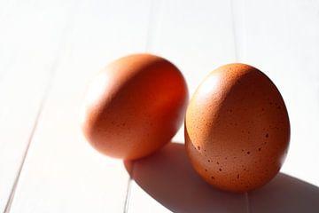 Twee eieren op een witte tafel in het zonlicht van