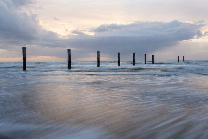 Strandpalen in de zee van Ton de Koning