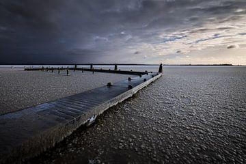 Een koude zonsopkomst in de winter boven het Lauwersmeer. Het water is bevroren en de stijger bedekt van Bas Meelker