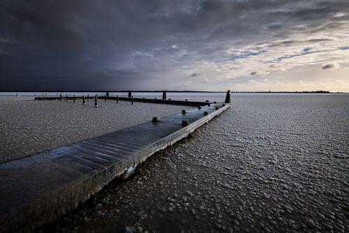 Een koude zonsopkomst in de winter boven het Lauwersmeer. Het water is bevroren en de stijger bedekt