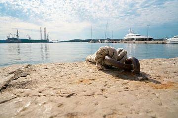 Touw voor het aanmeren van schepen en vissersboten aan een aanlegsteiger in de haven van Pula van Heiko Kueverling