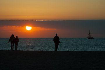 Wandelen op het strand met zonsondergang van Miranda Zwijgers
