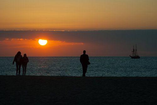 Wandelen op het strand met zonsondergang
