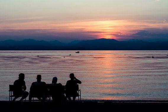 4 vrienden kijkend naar de ondergaande zon