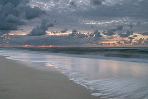 De branding op een strand op Vlieland tijdens zonsondergang