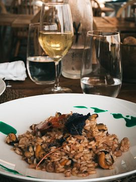 Verse seafood risotto met een glas Italiaanse wijn op het eiland Procida in Italië