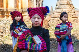 Drie meisjes verkopen katoenen sjaals bij de ruines van pagodes