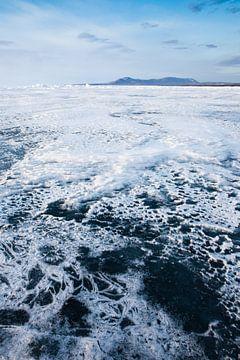 Dunne sneeuw vormt grillige patronen op het ijs van Baikal en bergen in de verte met de lucht van Michael Semenov