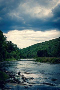 Een rivier op een donker bewolkte dag in de Belgische Ardennen omgeven door bergen en bos. van Joeri Mostmans