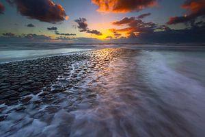 Overspoelde zeewering tijdens zonsondergang van