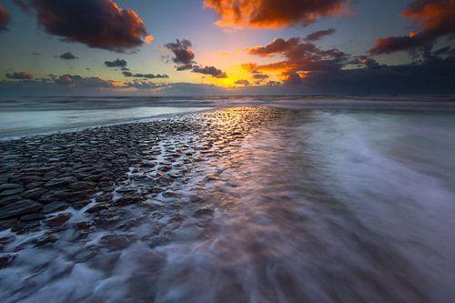 Overspoelde zeewering tijdens zonsondergang