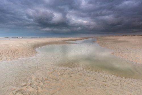 Regenwolken boven het Noordzeestrand Terschelling. van