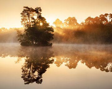 Warme zonsopgang boven een meer met een eilandje van Henno Drop