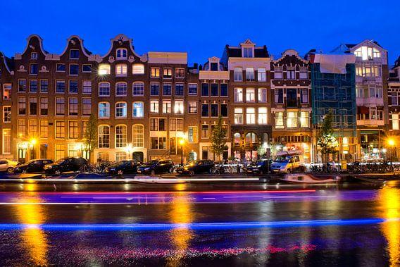 Amsterdamse gracht bij nacht met strepen van de rondvaartboot die tijdens de lange sluitertijd voorbij vaart.