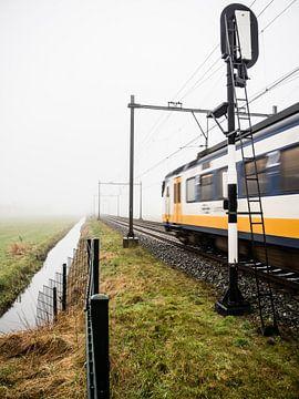 Een typische Nederlandse trein komt uit de mist en passeert een spoorwegsein. van Hans Post