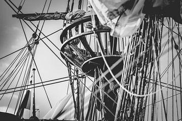 Zwart wit foto van Kraaiennest in de mast van een oude zeilboot van Fotografiecor .nl