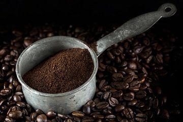 kleine metalen pot met gemalen koffie op een hoopje hele gebrande koffiebonen, donkere achtergrond,  van Maren Winter